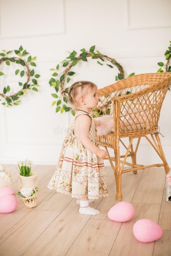 Bambina sveglia in un vestito con una stampa floreale nelle decorazioni di Pasqua nello studio Bambina con le uova di Pasqua ed i fotografie stock libere da diritti