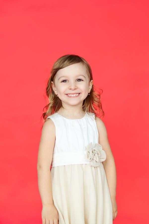 Bambina sveglia in vestito bianco che sorride sulla macchina fotografica immagini stock