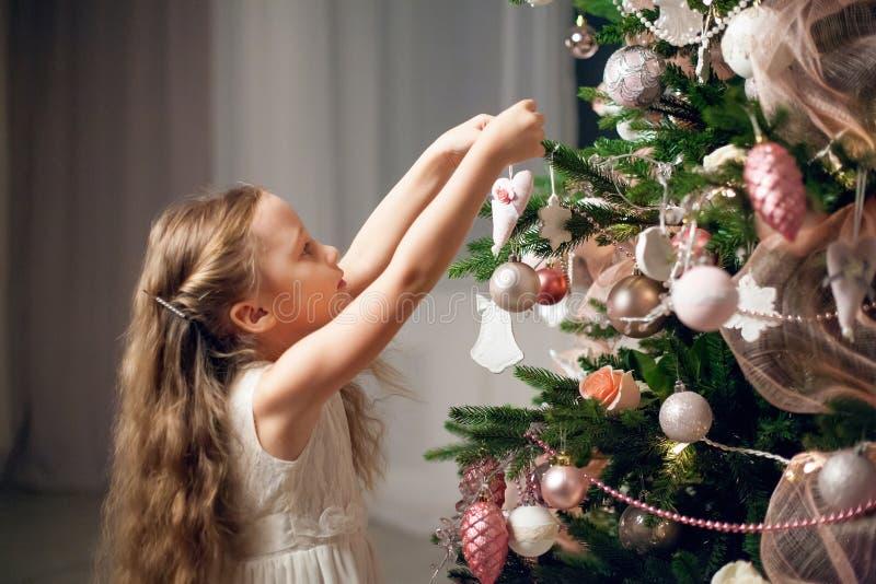 Bambina sveglia in vestito che decora l'albero di Natale fotografie stock libere da diritti