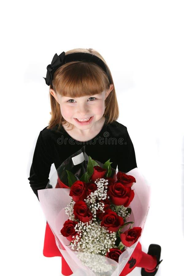 Bambina sveglia in vestito da festa con le rose rosse fotografie stock