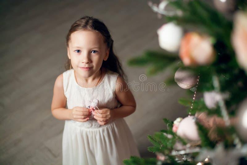 Bambina sveglia in vestito vicino all'albero di Natale immagine stock