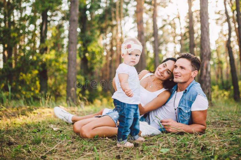 Bambina un anno sui precedenti dei genitori che riposano che si trovano sull'erba che impara camminare sulla natura nel parco I p immagine stock libera da diritti