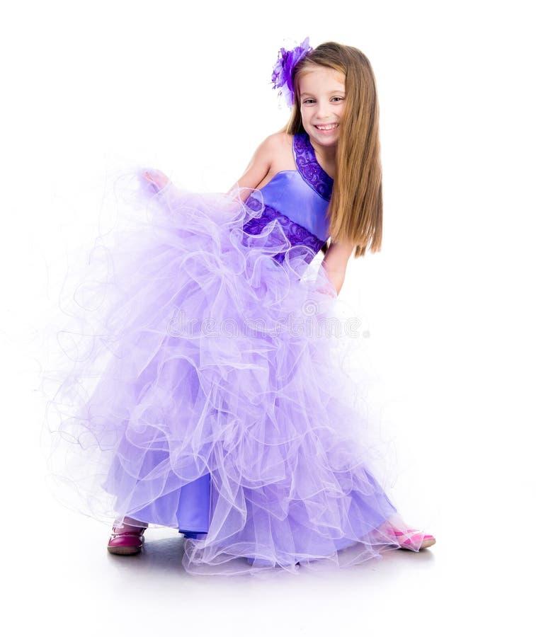 Bambina in un bello vestito porpora fotografia stock