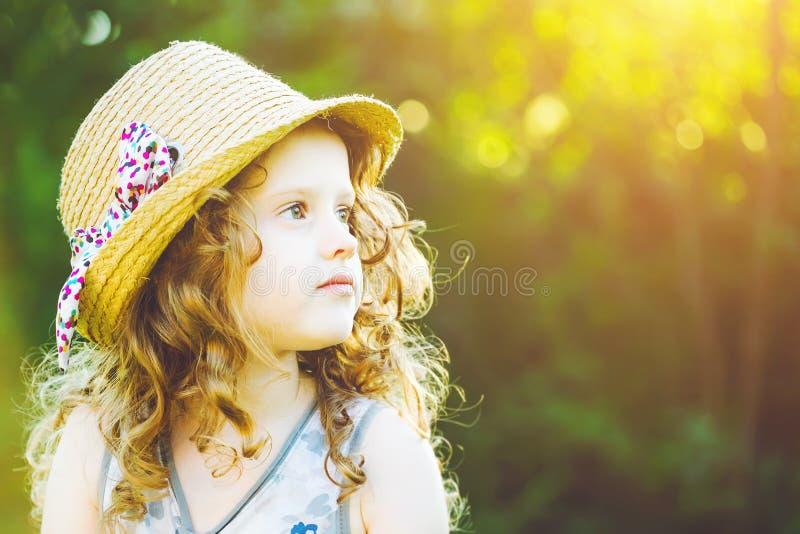 Bambina in un cappello di paglia al tramonto Concetto di libertà Tonalità della i immagine stock
