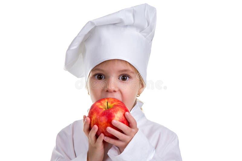 Bambina in un cappuccio del cuoco che morde la mela rossa Concetto di alimento sano e dello stile di vita sano Guardando diritto  fotografie stock libere da diritti