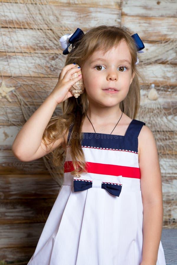 Bambina in un vestito elegante, con un fondo del muro di mattoni della conchiglia fotografia stock libera da diritti