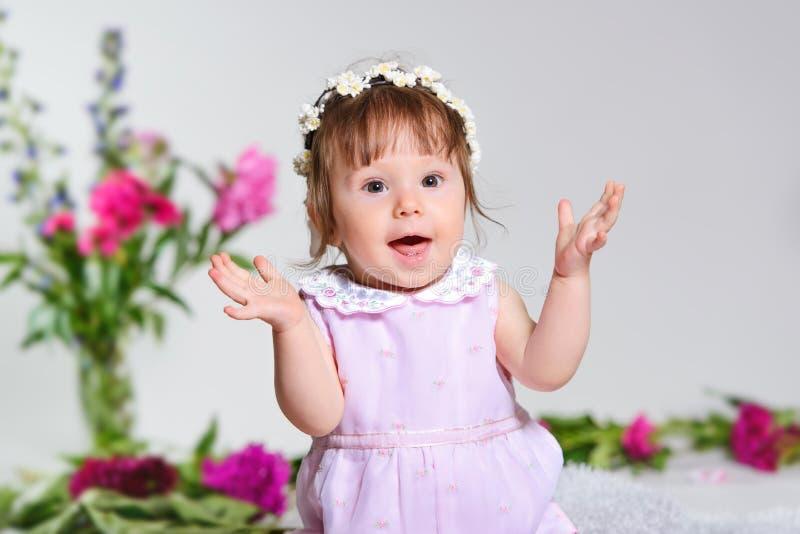 Bambina in un vestito rosa che si siede con un mazzo dei fiori rosa immagini stock libere da diritti