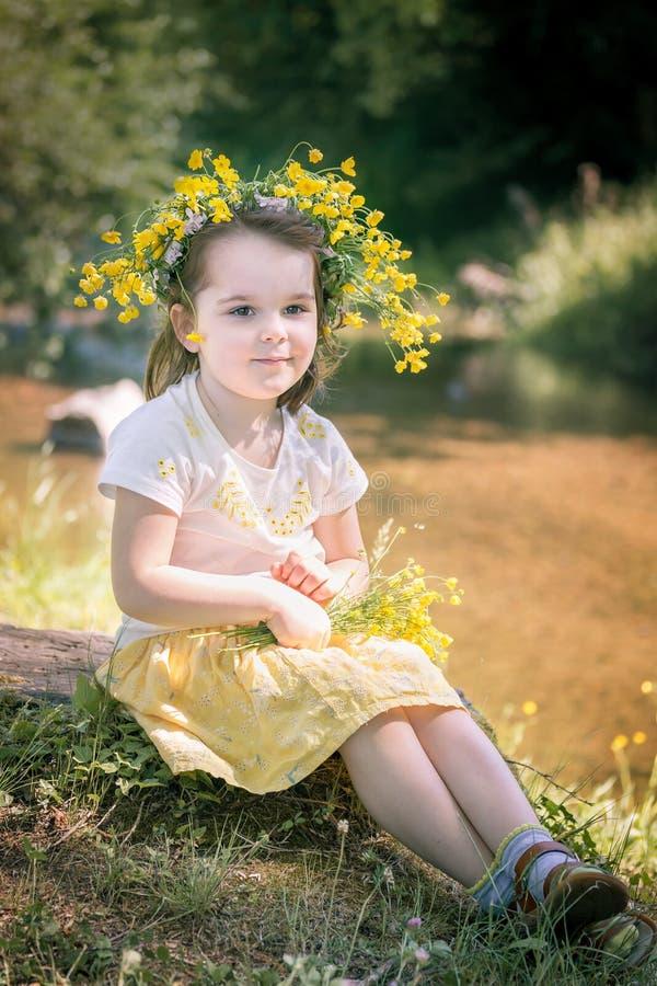 bambina in una corona dei fiori gialli fotografia stock