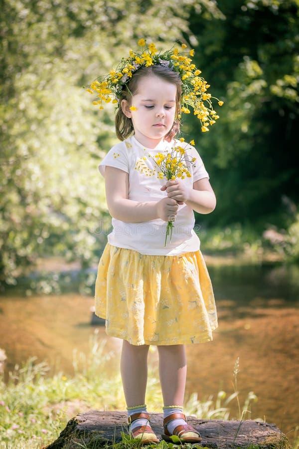 bambina in una corona dei fiori gialli fotografia stock libera da diritti