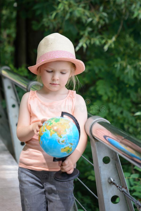 Bambina in una paglia Panama Il bambino considera il modello del globo immagini stock libere da diritti
