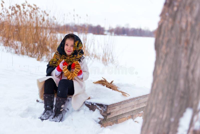 Bambina in una pelliccia con i bagel fotografia stock