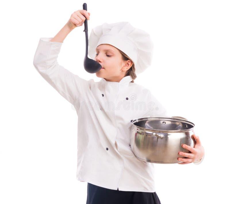 Bambina in uniforme del cuoco con la pentola e la siviera fotografia stock libera da diritti