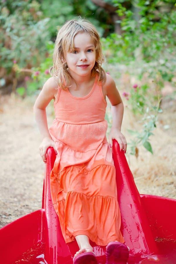 Bambina in uno stagno dell'iarda immagine stock
