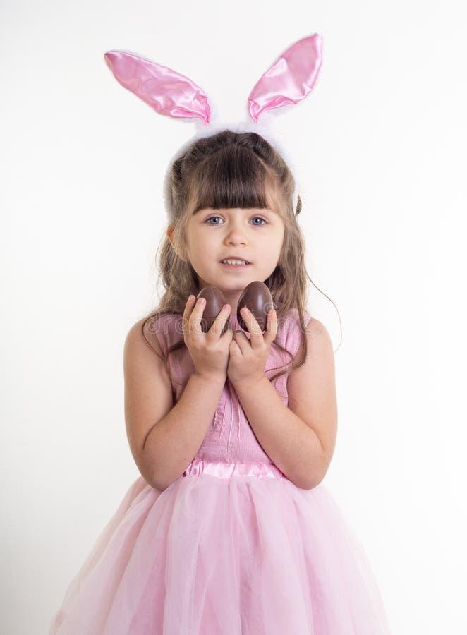 Bambina vestita come la condizione del coniglietto di pasqua sul fondo bianco e tenuta delle uova di Pasqua del cioccolato fotografia stock