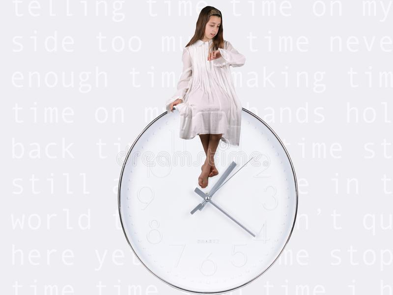 Bambina vestita nella seduta bianca sopra l'orologio bianco & d'argento che dice il tempo sull'orologio immagini stock