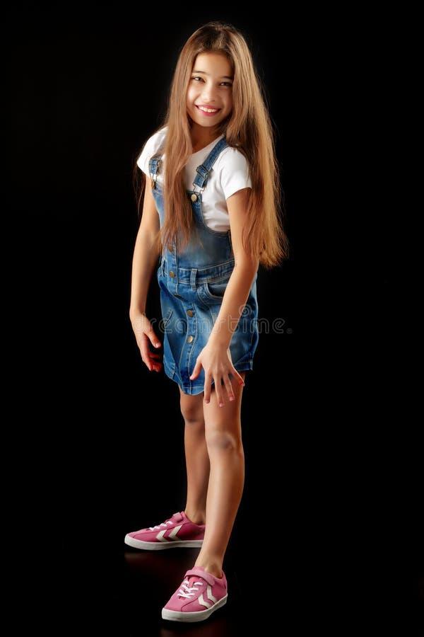 Bambina in vestiti del denim su un fondo nero immagini stock