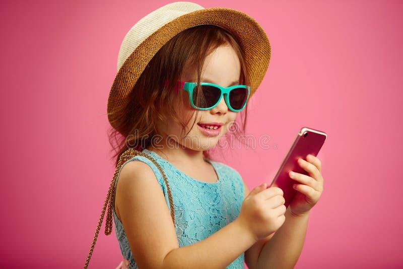 Bambina in vestiti di estate, portanti un cappello della spiaggia, occhiali da sole, esaminanti il telefono, supporti su fondo is fotografia stock
