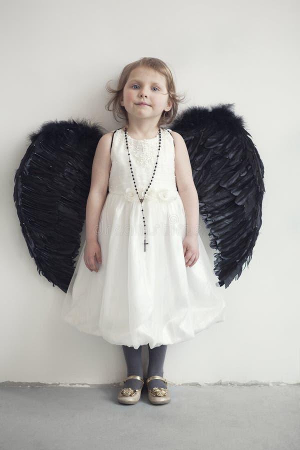 Bambina in vestito bianco con le ali nere artificiali fotografie stock libere da diritti