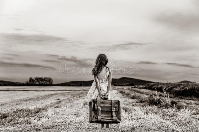 Bambina in vestito classico con la valigia di viaggio fotografia stock