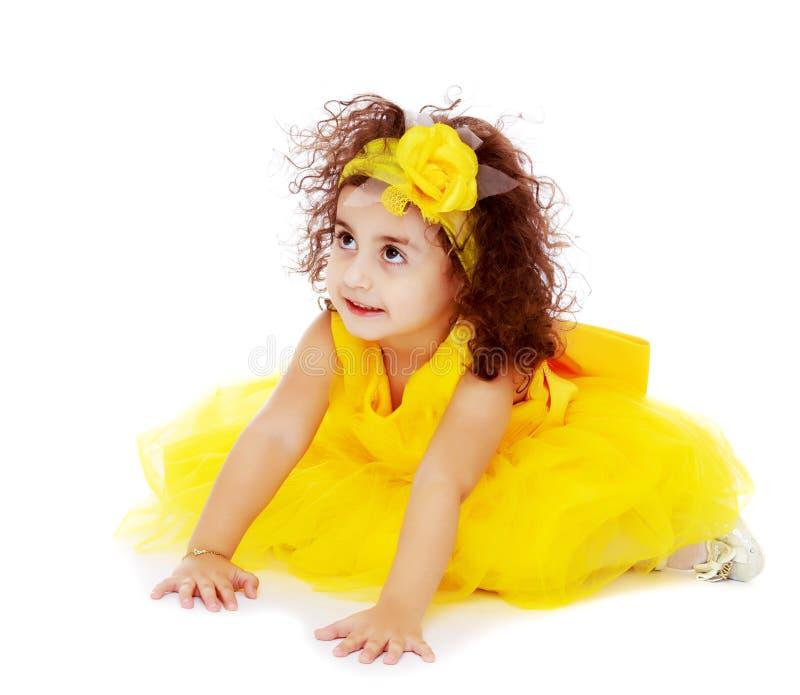 Bambina in vestito giallo che si siede sul pavimento immagini stock