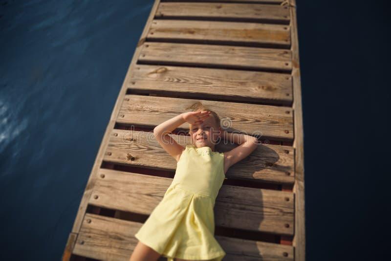 Bambina in vestito giallo che si trova al pilastro di legno fotografia stock