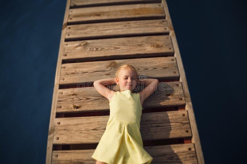 Bambina in vestito giallo che si trova al pilastro di legno con l'occhio chiuso fotografia stock