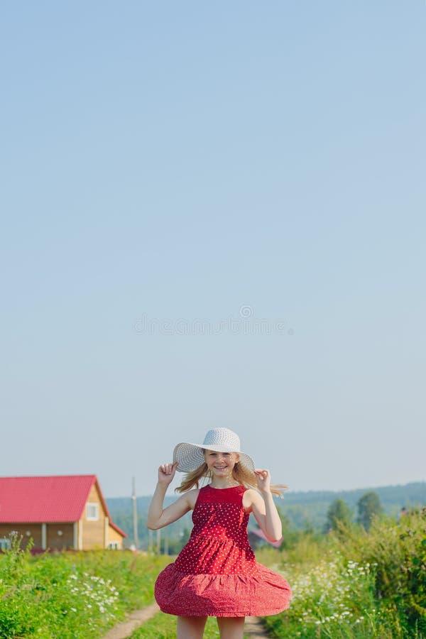Bambina in vestito rosso e cappello bianco con il grande bordo fotografia stock