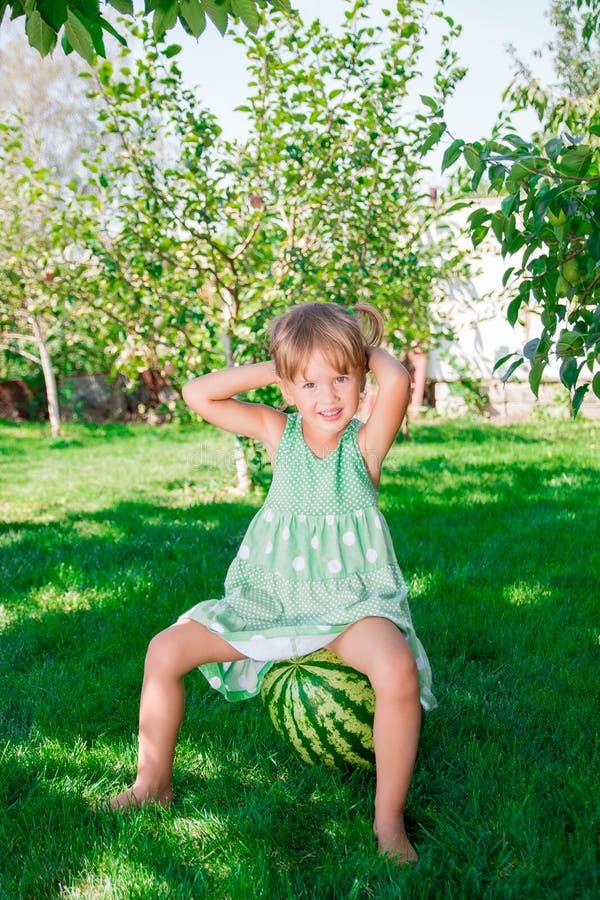 Bambina in vestito verde che si siede a piedi nudi sull'anguria nel parco immagini stock