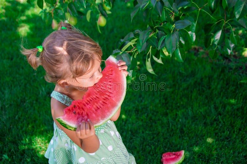 Bambina in vestito verde, stante a piedi nudi nel parco con la grande anguria della fetta fotografie stock