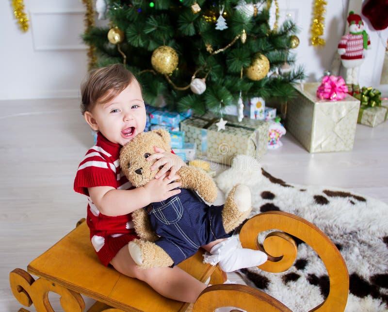 Bambina vicino ad un albero di Natale con i regali immagine stock libera da diritti