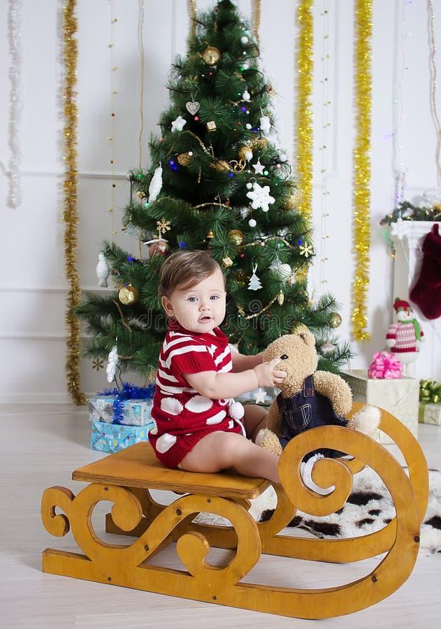Bambina vicino ad un albero di Natale con i regali fotografia stock libera da diritti