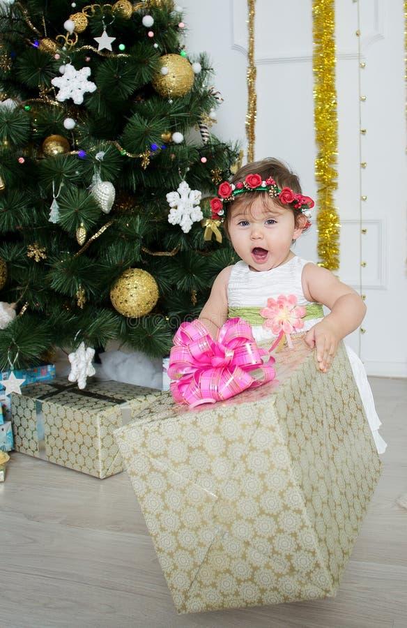 Bambina vicino ad un albero di Natale con i regali immagini stock libere da diritti
