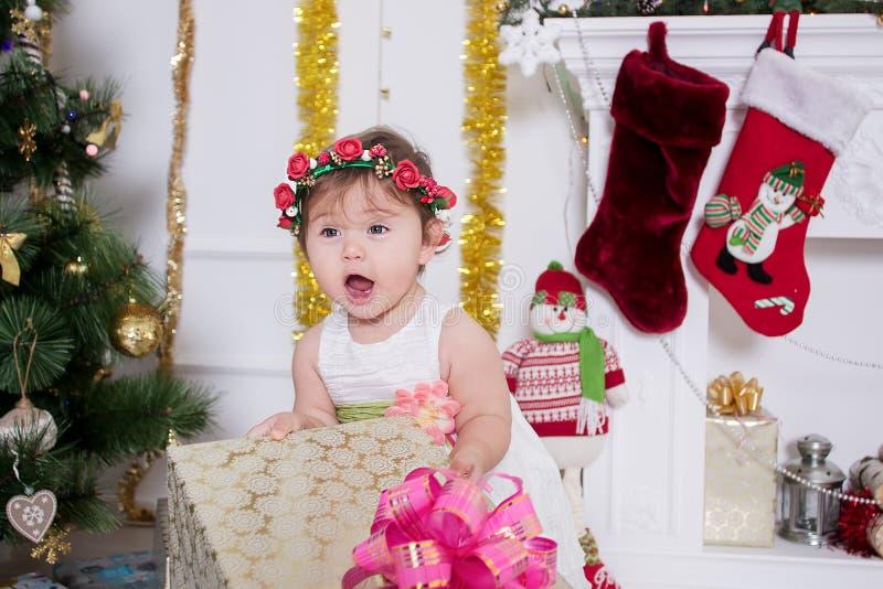 Bambina vicino ad un albero di Natale con i regali immagini stock