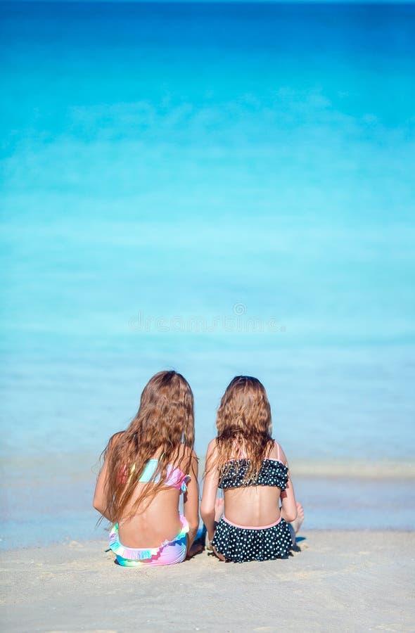Bambine adorabili che giocano con la sabbia sulla spiaggia Punto di vista posteriore dei bambini che si siedono in acqua bassa e  fotografie stock libere da diritti
