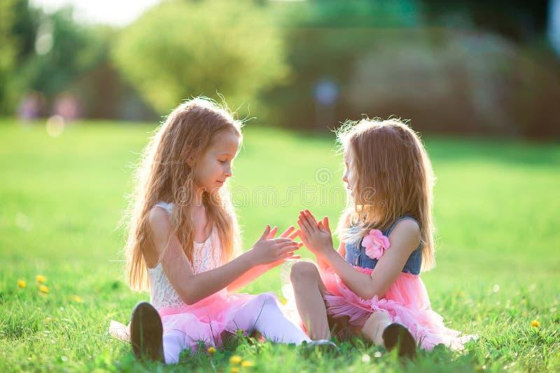 Bambine adorabili il giorno di molla all'aperto che si siede sull'erba fotografia stock
