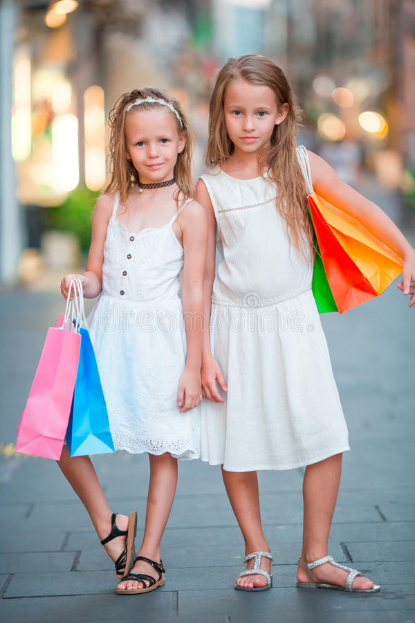 Bambine adorabili su acquisto Ritratto dei bambini con i sacchetti della spesa in piccola città italiana fotografia stock