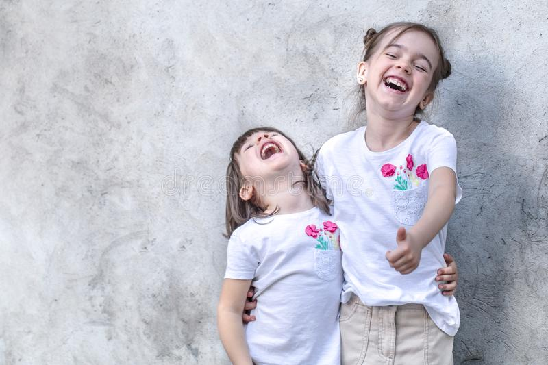 Bambine allegre su fondo strutturato grigio Bambina all'aperto del ritratto Fondo strutturato grigio della parete fotografia stock