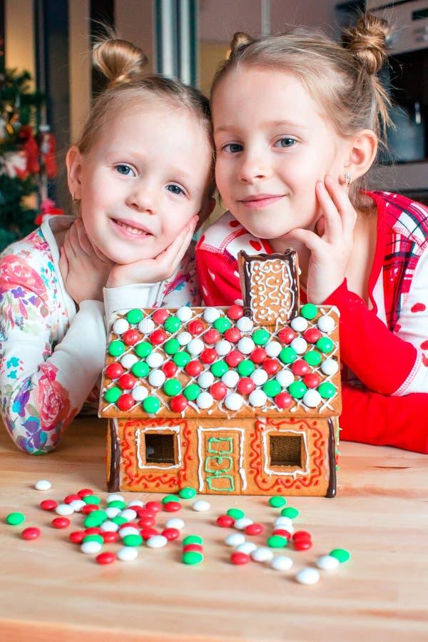 Bambine che fanno la casa di pan di zenzero di Natale al camino in salone decorato fotografia stock