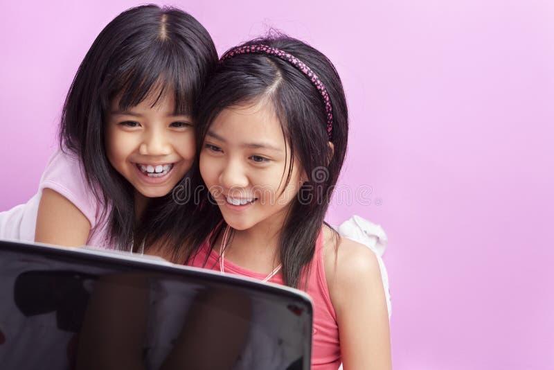 Bambine che giocano computer portatile fotografia stock libera da diritti