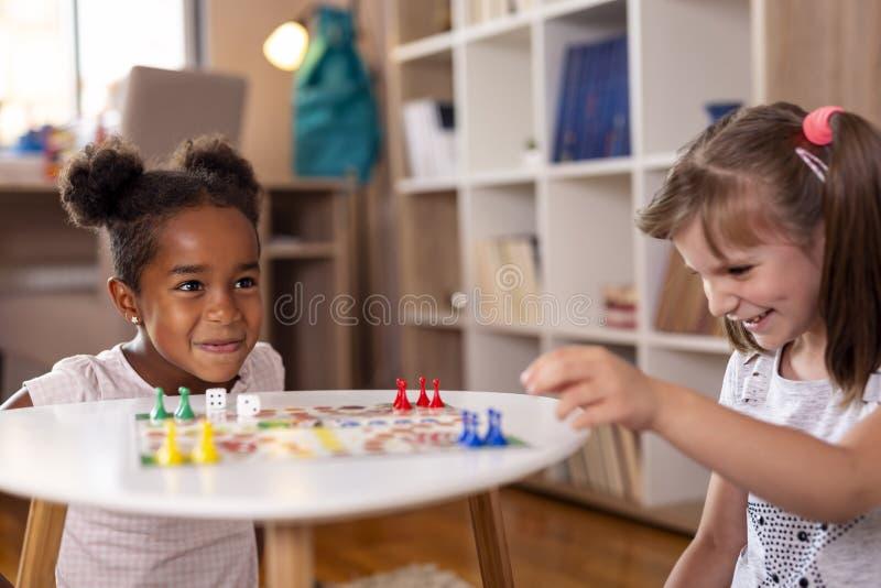 Bambine che giocano il gioco da tavolo di Ludo fotografia stock libera da diritti