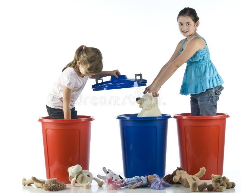 Bambine che giocano nell'i tamburi di plastica fotografia stock