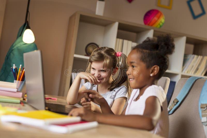 Bambine che guardano i fumetti sul computer portatile fotografie stock libere da diritti