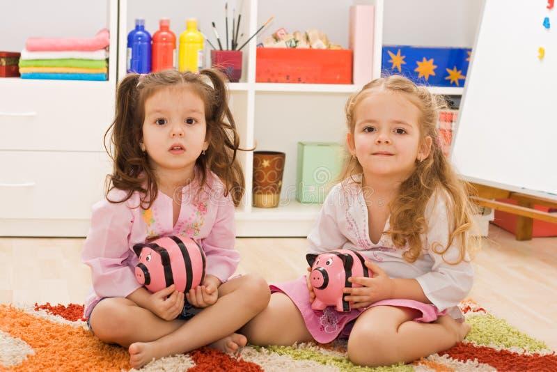 Bambine che tengono i piggybanks fotografia stock
