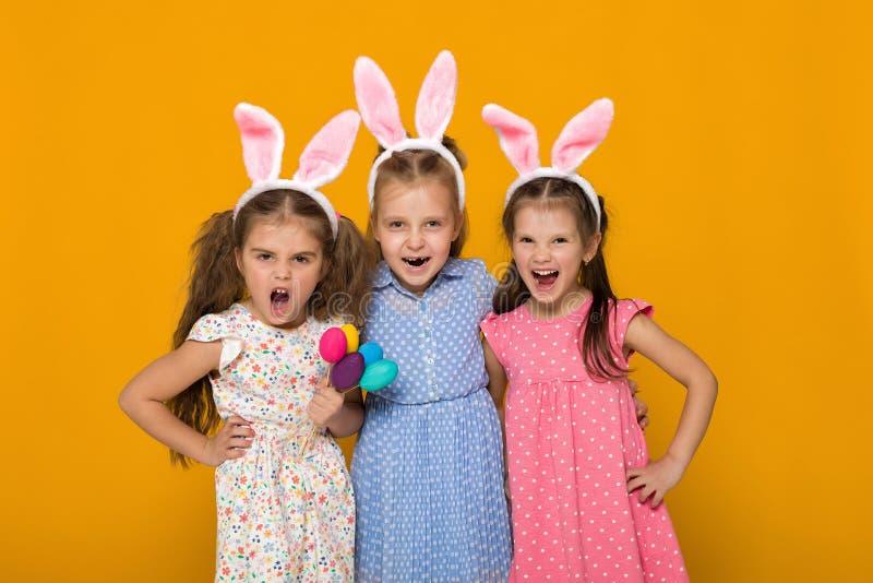 Bambine con le orecchie del coniglietto di pasqua che tengono le uova variopinte immagini stock libere da diritti