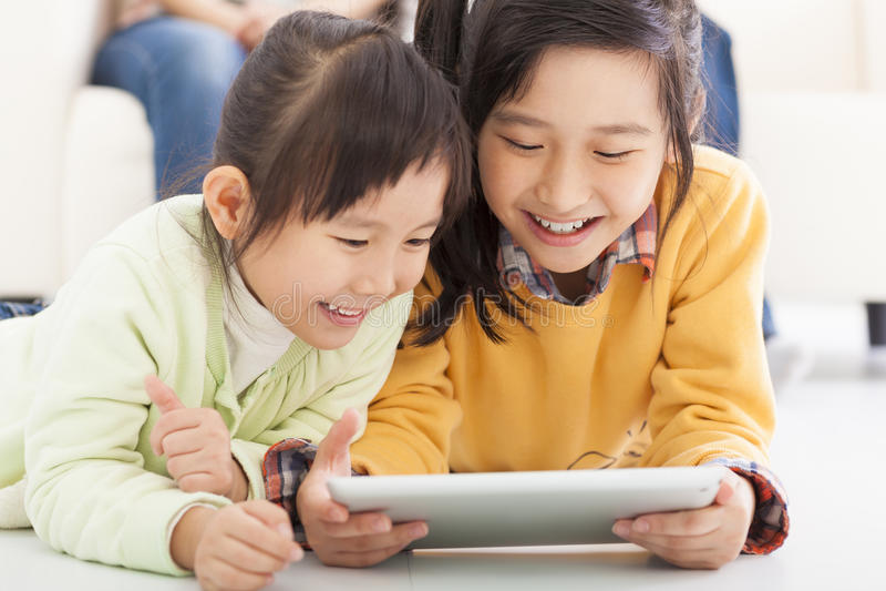 Bambine felici che per mezzo della compressa fotografie stock