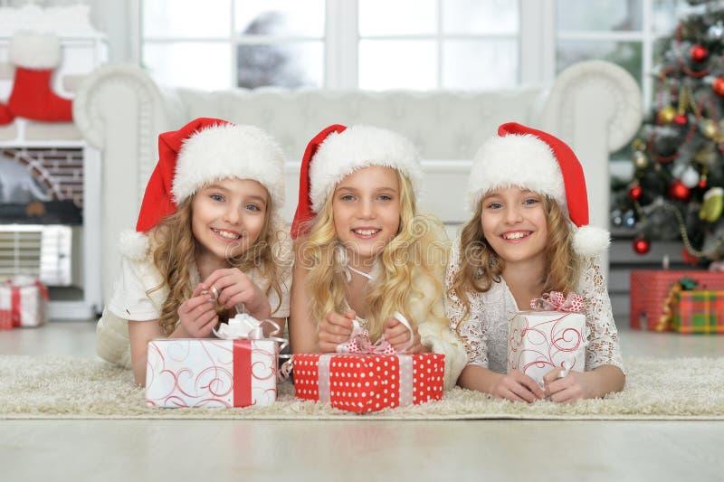 Bambine sveglie in cappelli di Santa che si trovano sul pavimento fotografia stock