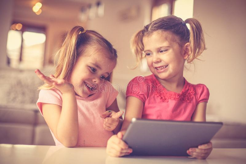 Bambine sveglie che giocano sulla linguetta digitale fotografie stock