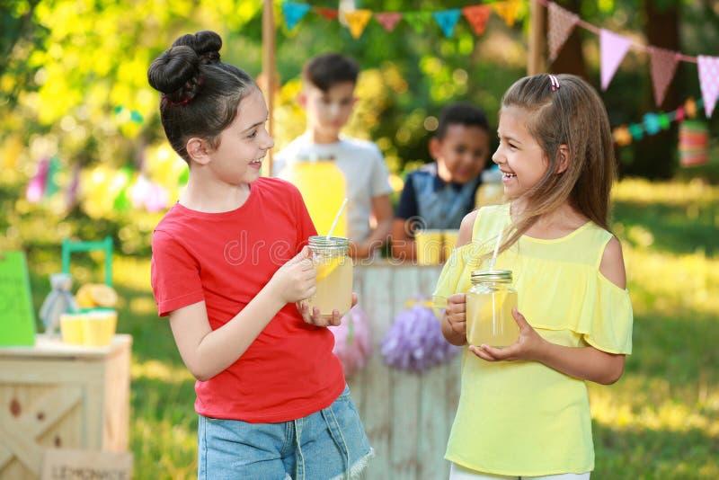 Bambine sveglie con limonata naturale Bevanda di rinfresco di estate fotografia stock