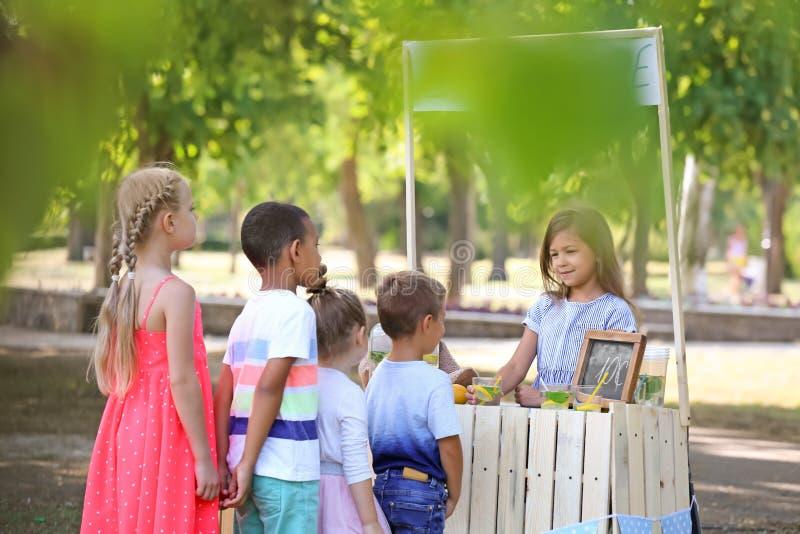 Bambini adorabili che aspettano nella coda la limonata naturale vicino al supporto in parco fotografie stock