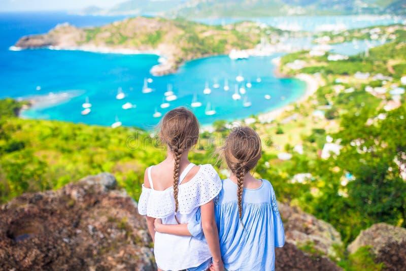 Bambini adorabili che godono della vista del porto inglese pittoresco all'Antigua in mare caraibico fotografia stock
